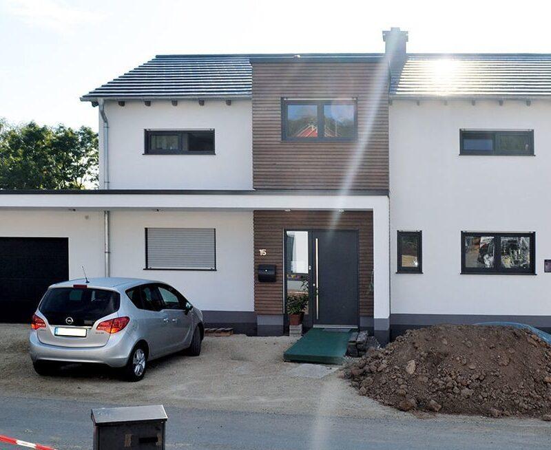 Modernes zweigeschossiges Haus mit Satteldach und mit Holz verkleidetem Erker