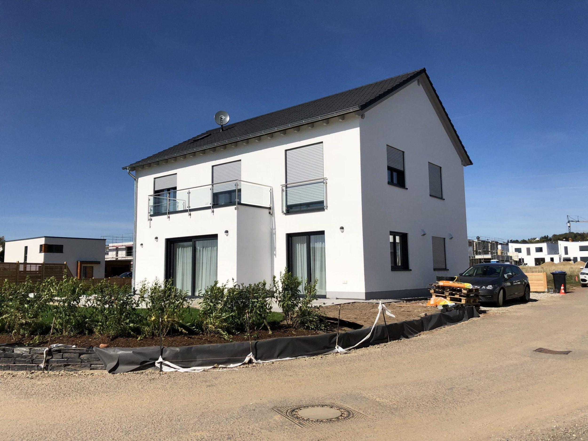 Neubau Einfamilienhaus mit Balkon, Satteldach, mit Hintergarten von Sträuchern umsäumt