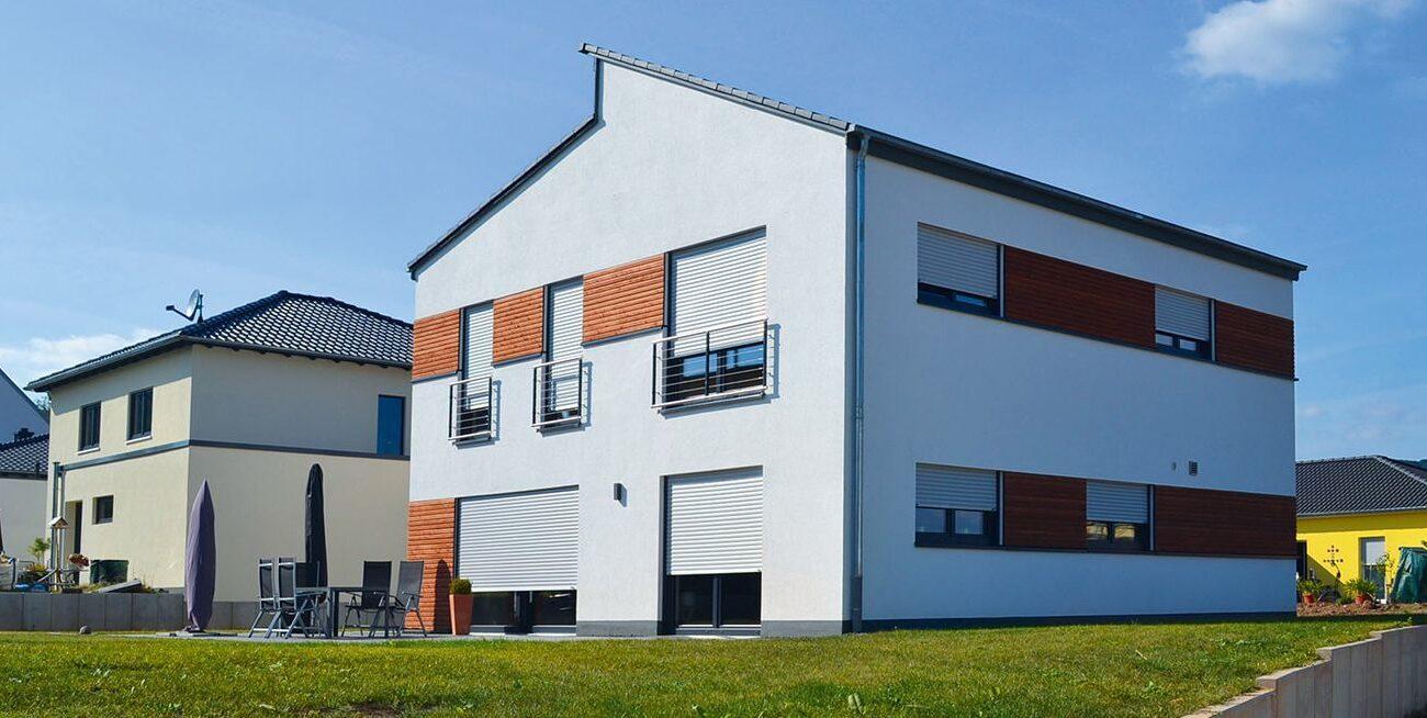 Zwei vollgeschossiges Einfamilienhaus mit versetzten Pultdächern, Vorbau und integrierter Garage, mit Rhombusleisten aus Holz