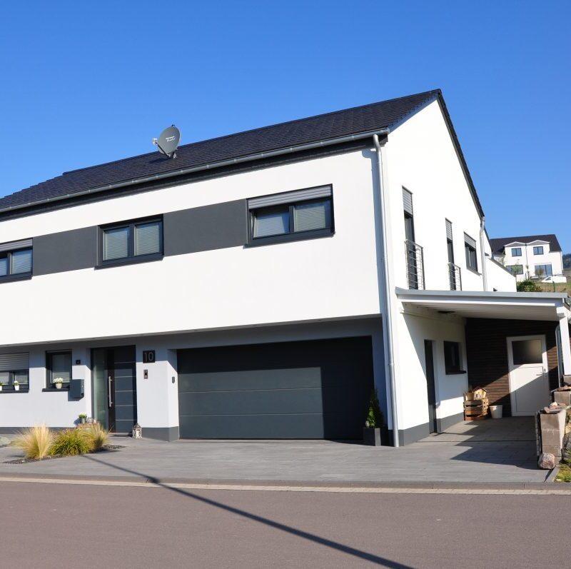 Einfamilienhaus auf abfallendem Grundstück, Wohnbereiche auf verschiedenen Ebenen im Split-Level angeordnet, mit integrierter Garage