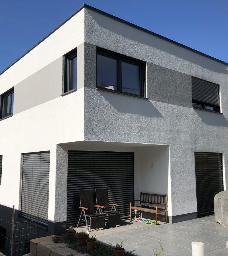 Doppelhaushälfte mit externem Kellerzugang, am Bauhausstil angelehnte Grundform mit zwei vollgeschossen und Flachdach