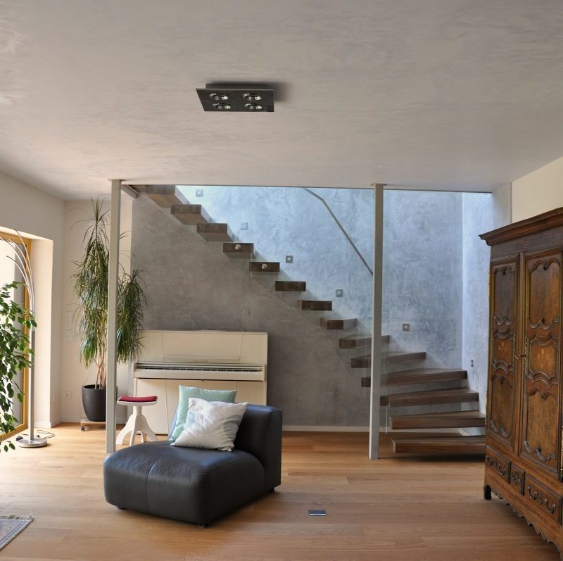 Wohnzimmer mit Treppenaufstieg ins Obergeschoss