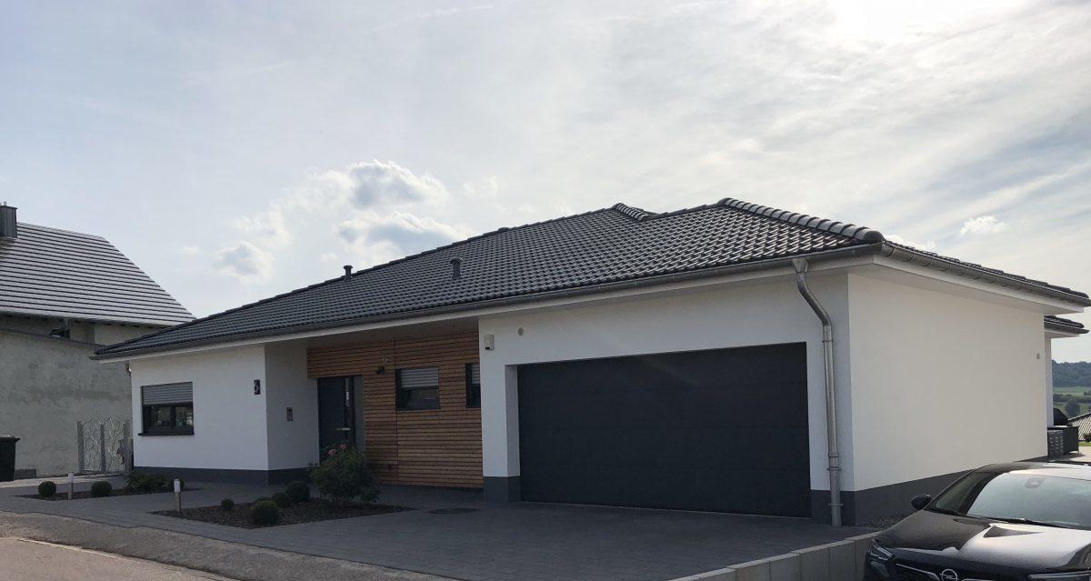 Einfamilienhaus im Bungalow-Stil mit integrierter Garage, teilweise Holz vertäfelter Fassade