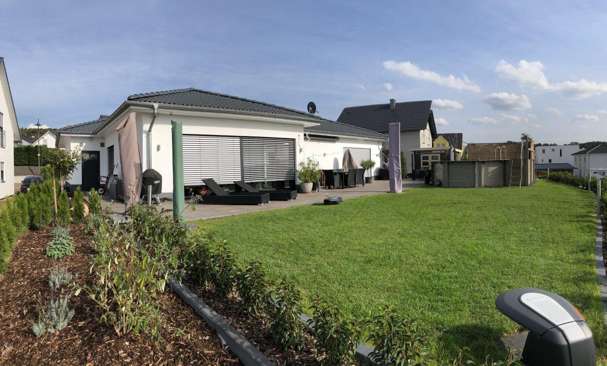 Moderner Neubau bodentiefen Fenstern und großem Garten