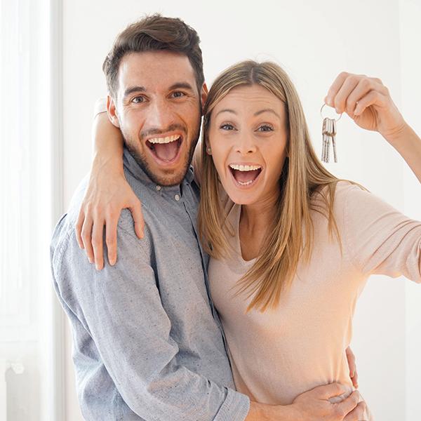 Glückliches Pärchen mit Haustürschlüssel in der Hand